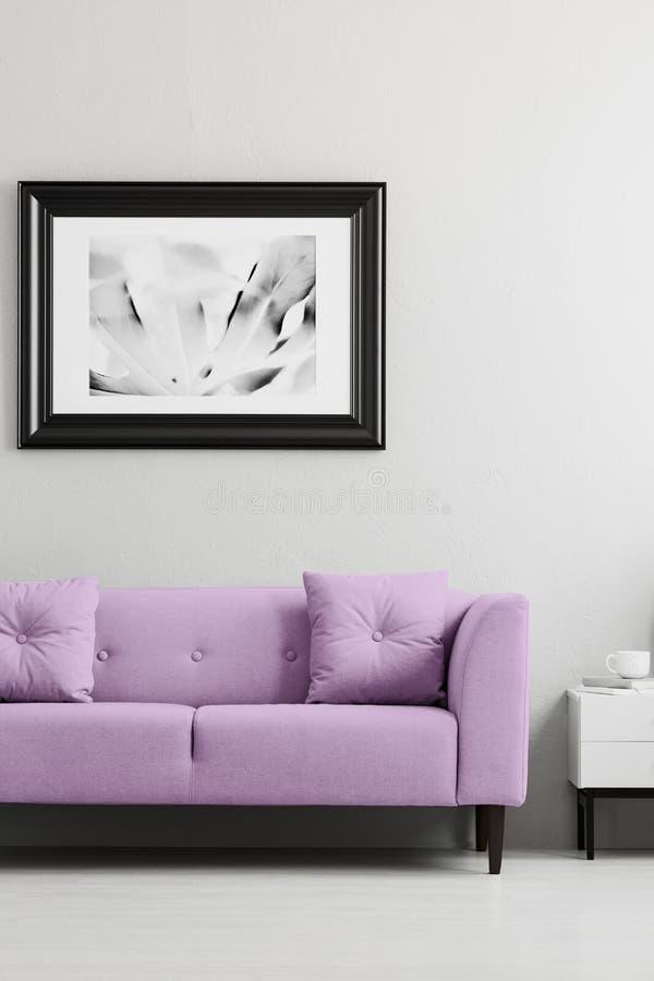 Lavendellilor, moderiktig soffa och en inramad fotomodell i en grå vardagsruminre med stället för en lampa royaltyfria foton