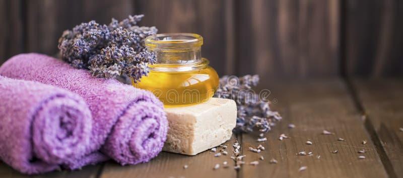 Lavendelolja, handdukar, naturlig tvål på träbakgrund, inställning för lavendelbrunnsortstilleben arkivfoto