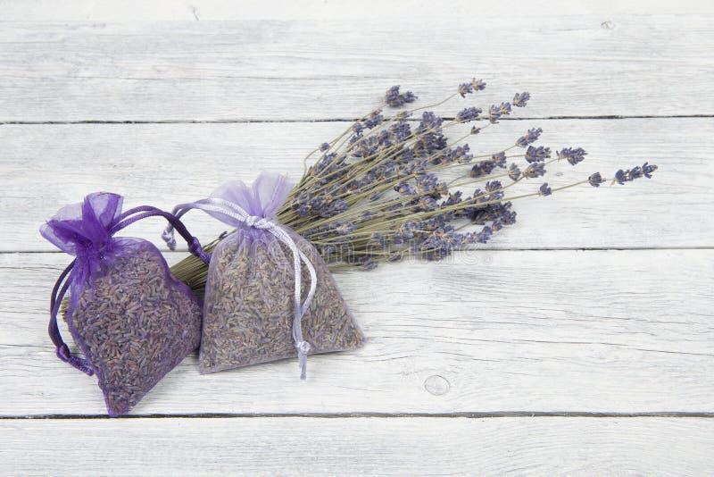 Lavendelpåsar och en grupp av torkade lavendelblommor på en vit träplankabakgrund arkivbild