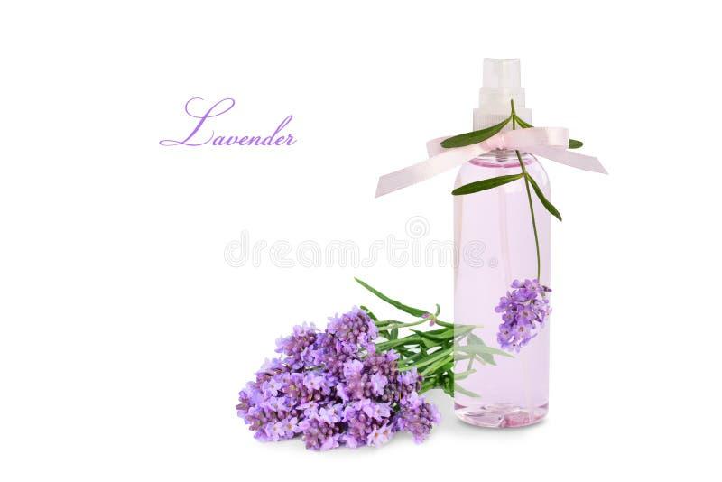 Lavendelprodukt i den isolerade sprejflaskan och blommor arkivfoto