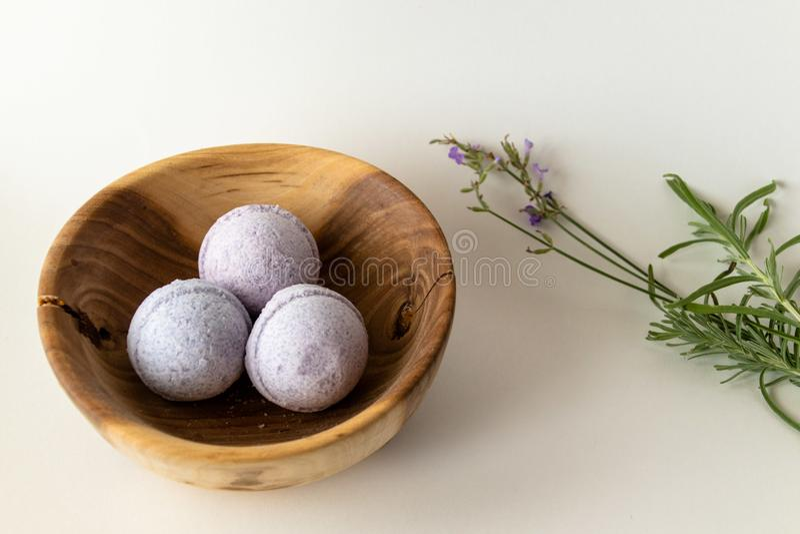 Lavender βόμβες λουτρών σε ένα ξύλινο κύπελλο με lavender τα μοσχεύματα στοκ φωτογραφίες