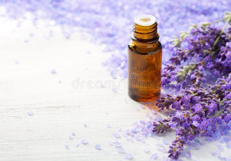 Lavender ουσιαστικό έλαιο, κλαδάκια lavender και ορυκτά άλατα λουτρών στον ξύλινο πίνακα Εκλεκτική εστίαση στοκ εικόνες