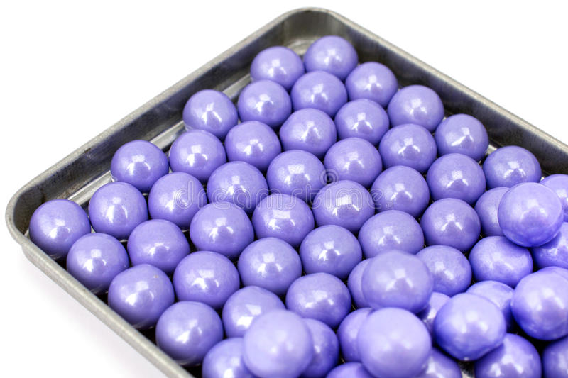 Lavender colored candies in a tin tray. Pretty purple pearlescent candies gleam in a galvanized tin tray. Isolated on a white background. Colored, lavender stock photos