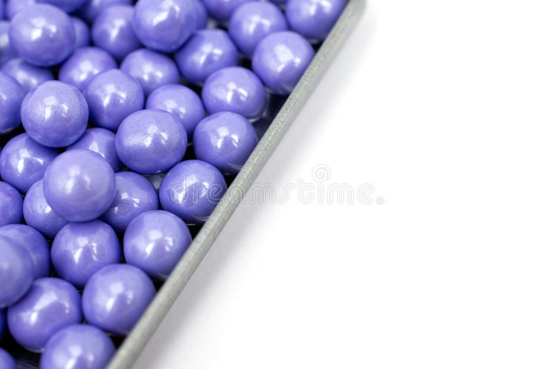 Lavender colored candies in a tin tray. Pretty purple pearlescent candies gleam in a galvanized tin tray. Isolated on a white background. Colored, lavender stock images