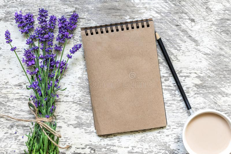 Lavender flowers bouquet, blank vintage notebook with pencil and cup of cuppuccino over white wooden table. top view royalty free stock photos
