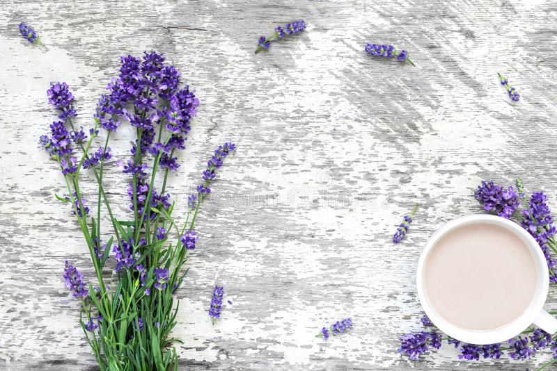 Lavender flowers bouquet with cup of cappuccino and frame made of flowers on rustic wooden background. top view stock images