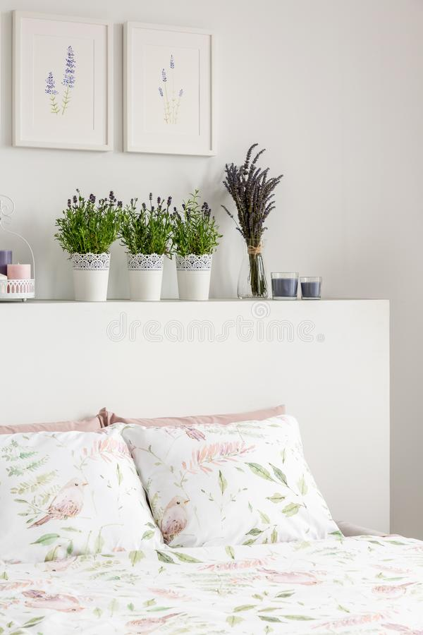 Lavender flowers on headboard of bed with pillows in white bedroom interior with posters. Real photo royalty free stock photos