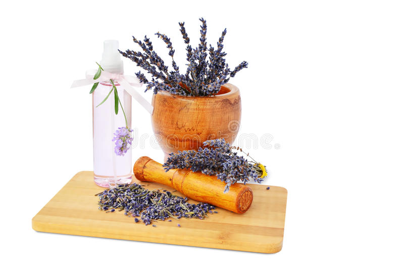 Lavender flowers in mortar, hydrosol bottle isolated. Lavender flowers in mortar, hydrosol bottle on wooden board isolated on white background stock image