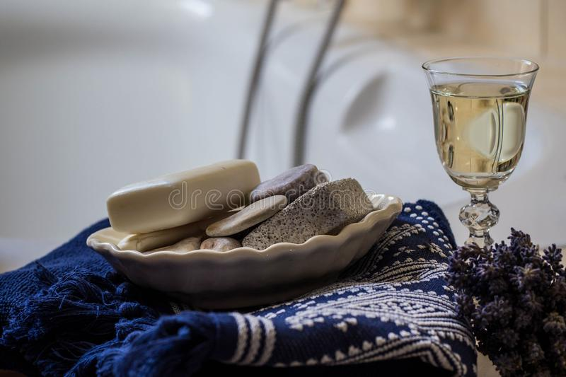 Lavender flowers, towel, bathroom accessories and a glass of white wine - home spa royalty free stock photo