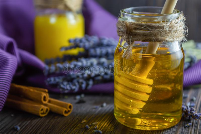 Lavender and herbal honey in glass jars with honey spoon on dark wooden background royalty free stock image