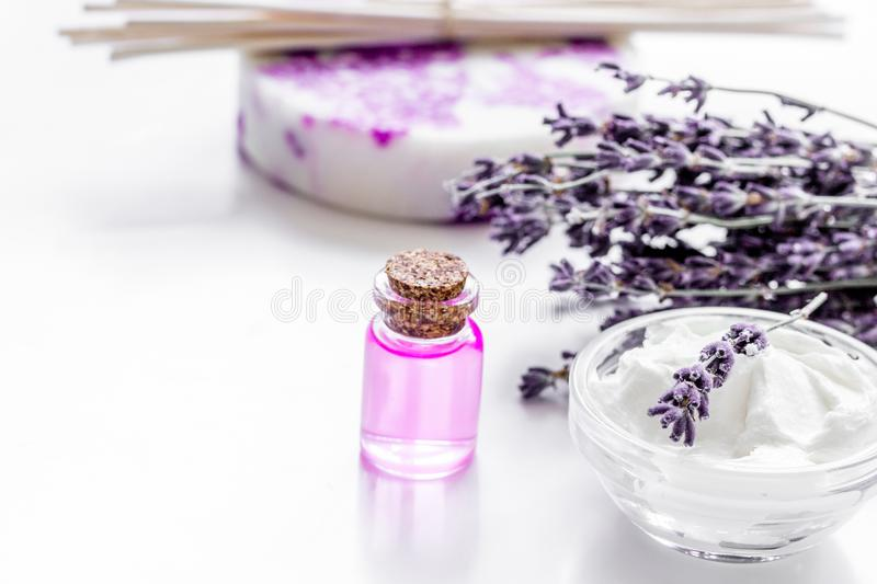 Lavender herbs in body care cosmetics with oil on white table ba. Lavender herbs in body care cosmetics with aroma oil on white table background royalty free stock photo