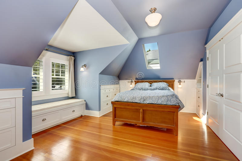 Lavender interior of attic bedroom with queen size bed royalty free stock images