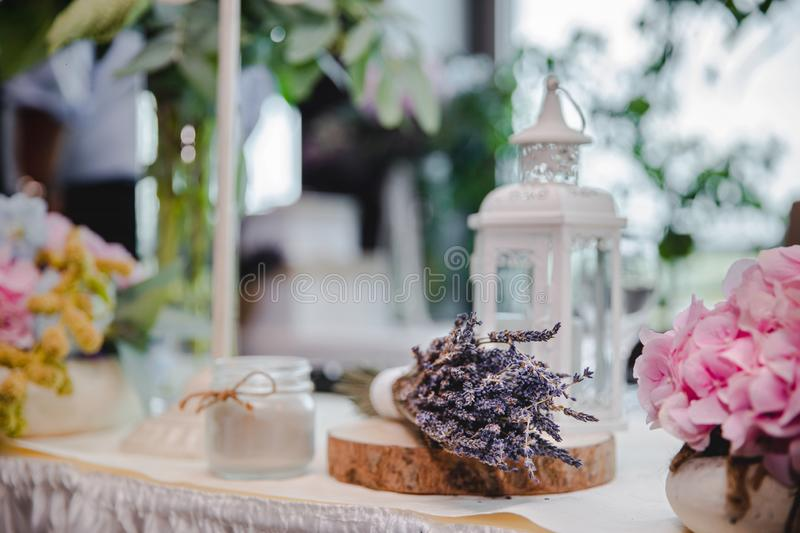 Lavender and other flowers for decoration. Table decoration for special occasion. Candles, flowers, wood stock image