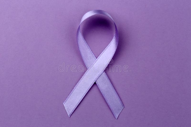 Lavender ribbon on color background. Cancer and epilepsy concept stock photography