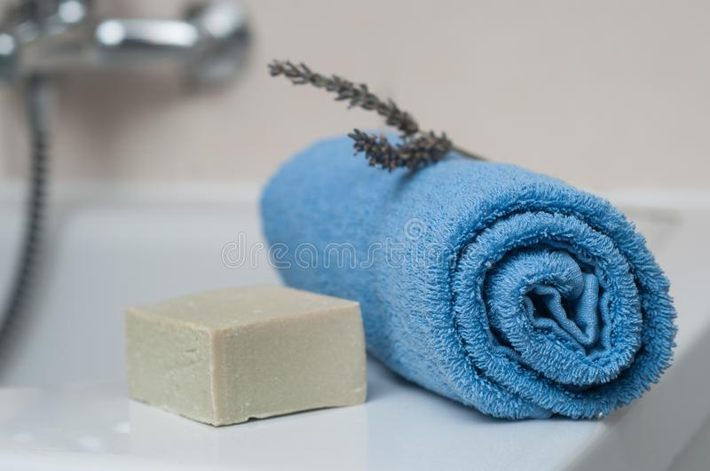 lavender soap and rolled blue towel in the bathroom stock image