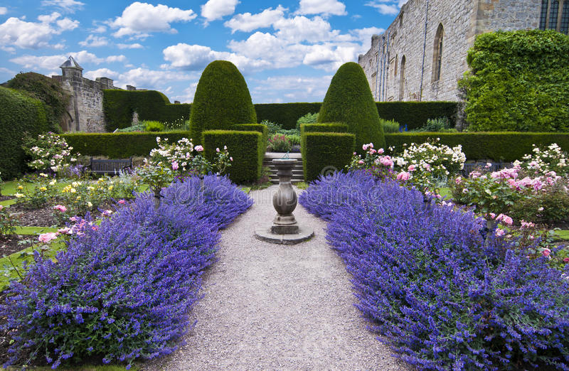 Lavender sundial. Gravel path leading to an old sundial between beds of lavender in a formal garden setting royalty free stock image