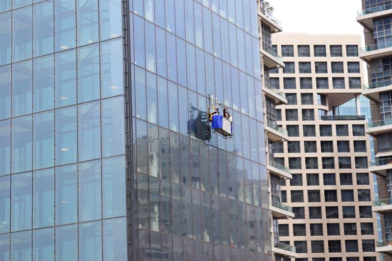 Laveurs de vitres accrochant sur leur panier photos stock