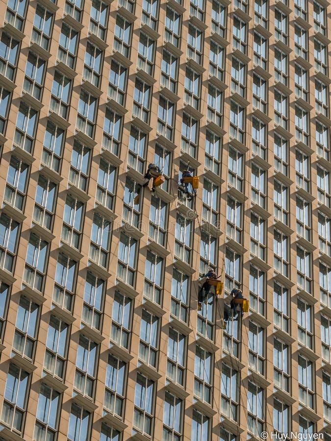 Laveurs de vitres en dehors des immeubles des bureaux images stock