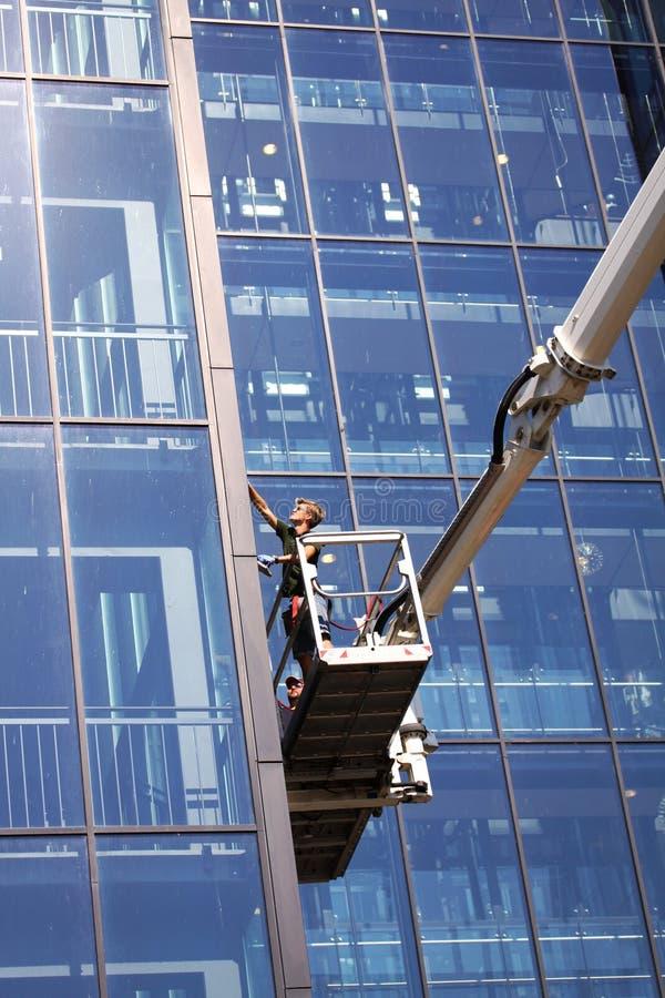 Laveurs de vitres travaillant à un bâtiment en verre ayant beaucoup d'étages moderne image libre de droits
