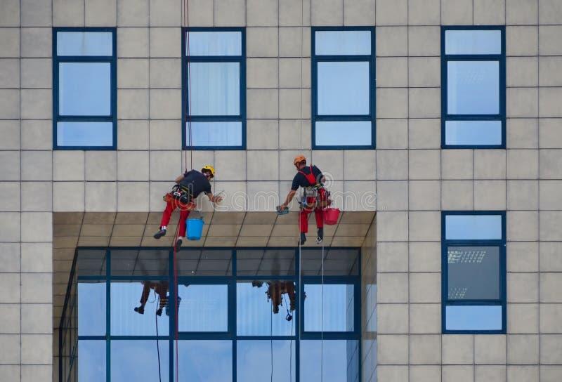 Laveurs de vitres travaillant au bâtiment, nettoyant la façade image stock