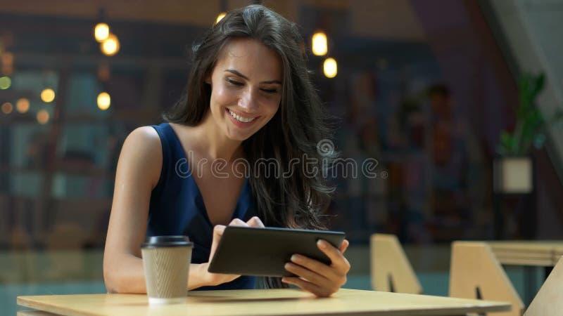 Lavorando al caffè Giovane bella donna lunga dei capelli che si siede alla tavola e che utilizza il computer della compressa nel  immagini stock