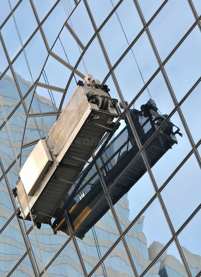 Lavorando alla parete di vetro esterna di costruzione fotografie stock libere da diritti