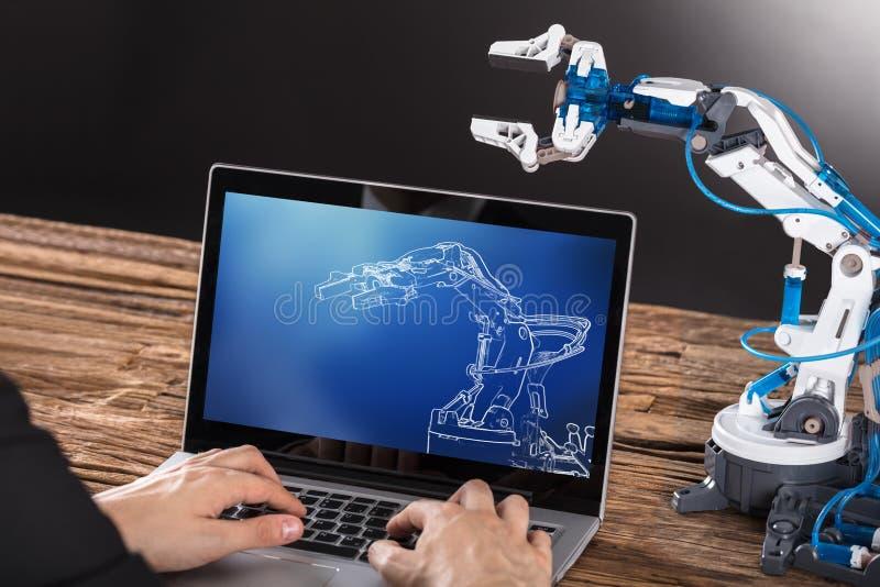 Lavorando alla progettazione del braccio del robot industriale sul computer portatile fotografia stock libera da diritti