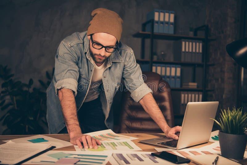 Lavorando alle carte dei documenti della lettura del tipo del capo di notte indossa il supporto casuale dell'attrezzatura vicino  fotografie stock