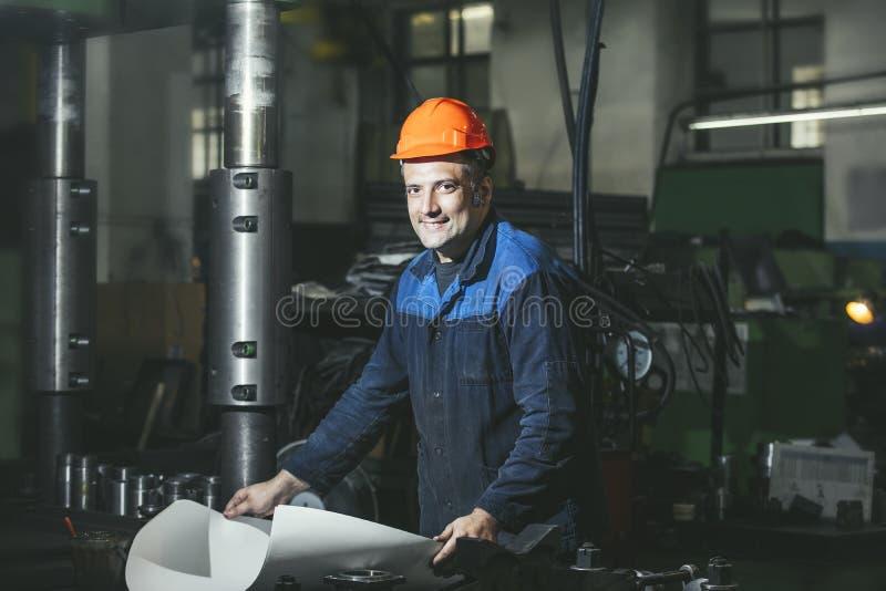 Lavorando nella produzione contro un fondo delle macchine dal immagine stock