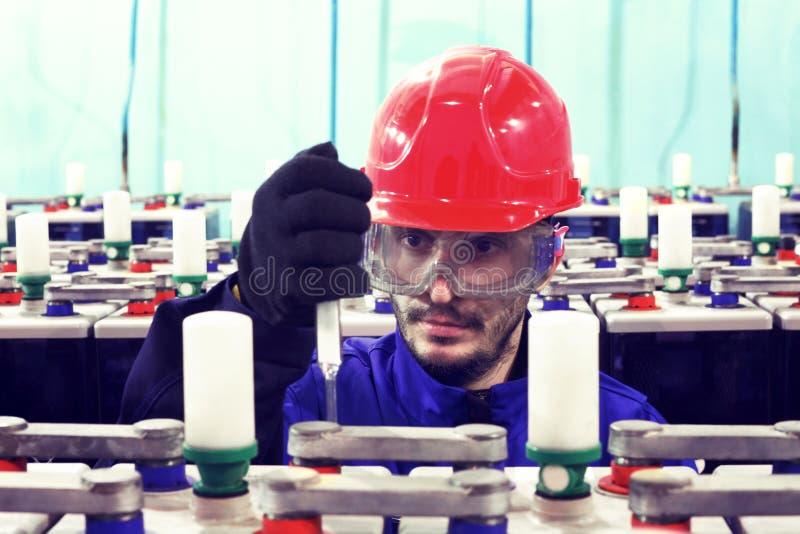 Lavorando in un casco prende le misure sull'attrezzatura immagine stock libera da diritti