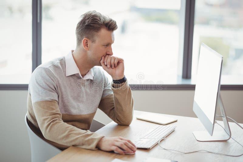 Lavorare esecutivo attento al personal computer allo scrittorio fotografie stock