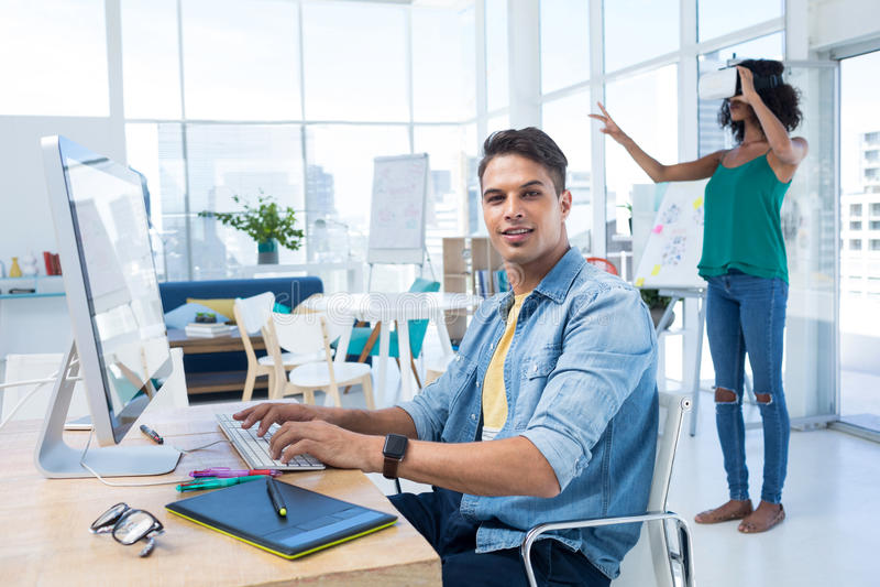 Lavorare esecutivo maschio al computer mentre dirigente femminile che per mezzo della cuffia avricolare di realtà virtuale fotografia stock libera da diritti