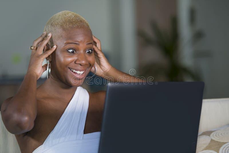 Lavorare sorridente della giovane bella donna afroamericana nera felice al computer portatile a casa rilassato sullo strato del s fotografia stock