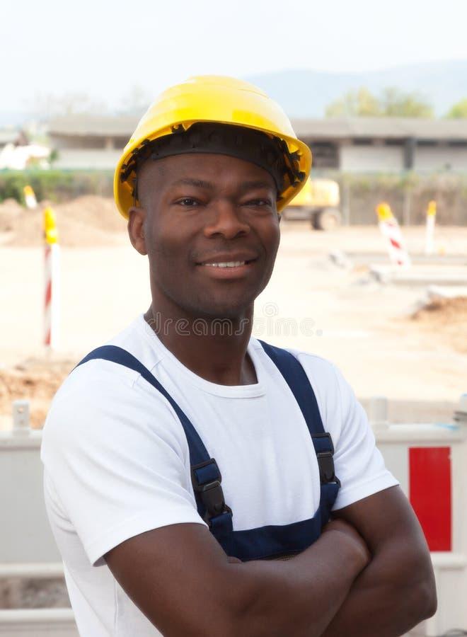 Lavoratore africano al cantiere che esamina macchina fotografica fotografia stock libera da diritti