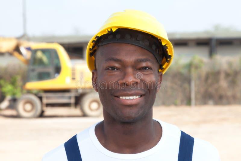 Lavoratore africano di risata al cantiere con  immagini stock