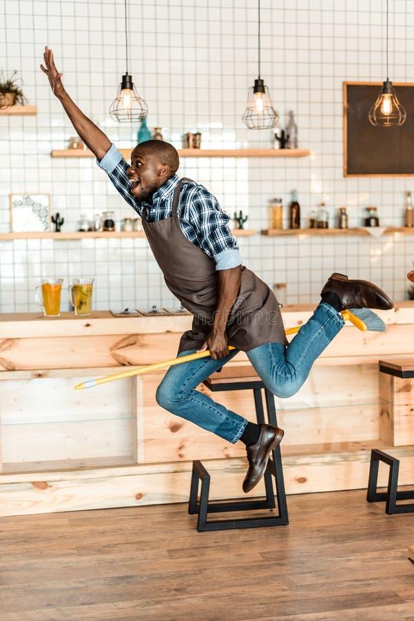 lavoratore afroamericano bello emozionante divertendosi e saltando con la scopa immagine stock libera da diritti