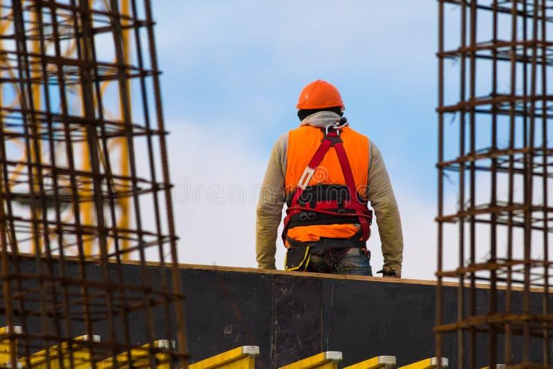 Lavoratore in arancia con la cintura di sicurezza sul cantiere immagini stock libere da diritti