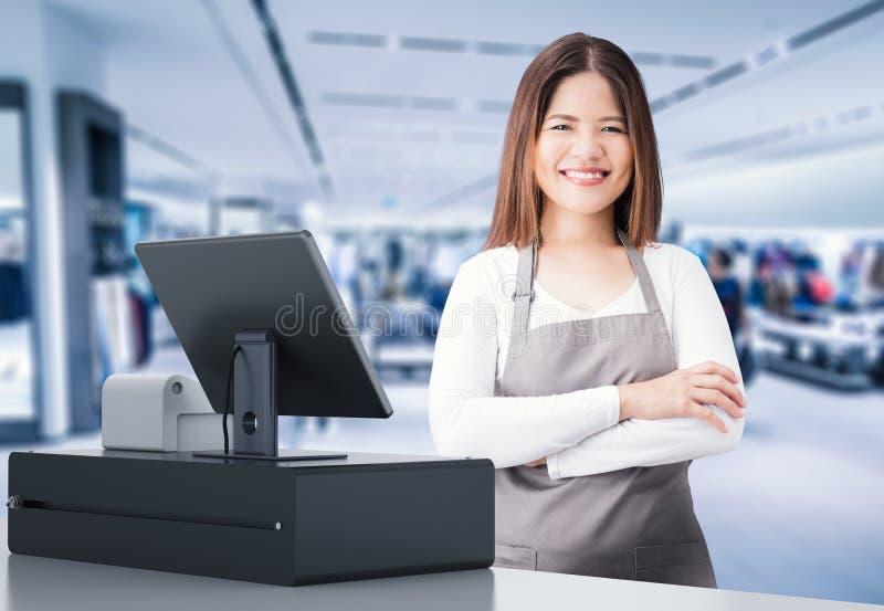 Lavoratore asiatico con lo scrittorio di cassiere fotografie stock