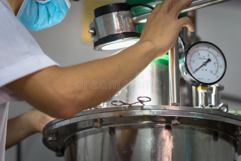 Lavoratore asiatico del primo piano che lavora con la macchina del fermento immagini stock libere da diritti