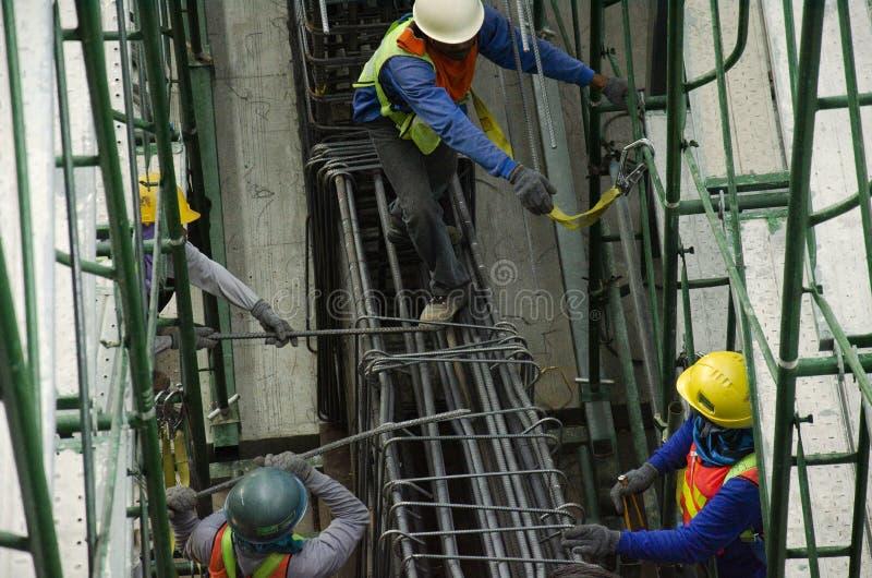 Lavoratore asiatico della gente che tricotta le barre dei coni retinici di metallo nel rinforzo della struttura per il versamento fotografia stock
