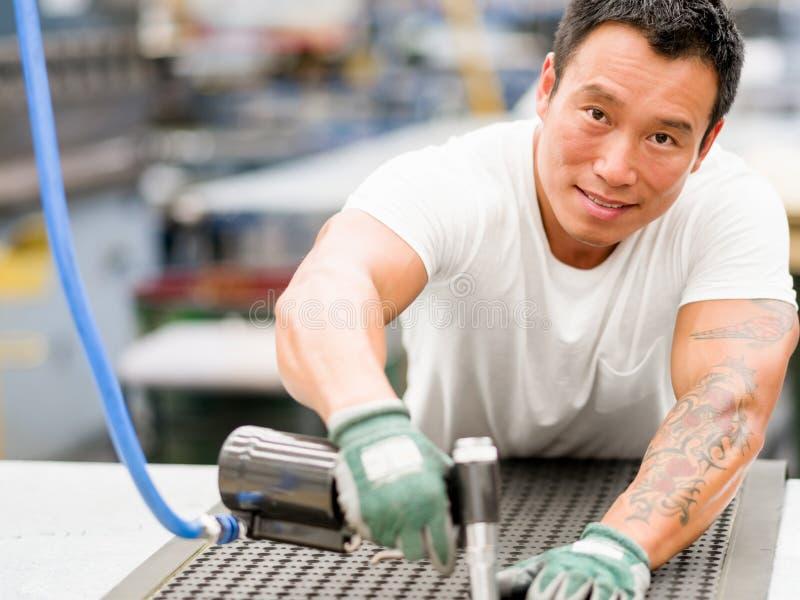 Lavoratore asiatico in impianto di produzione sul pavimento della fabbrica fotografia stock libera da diritti