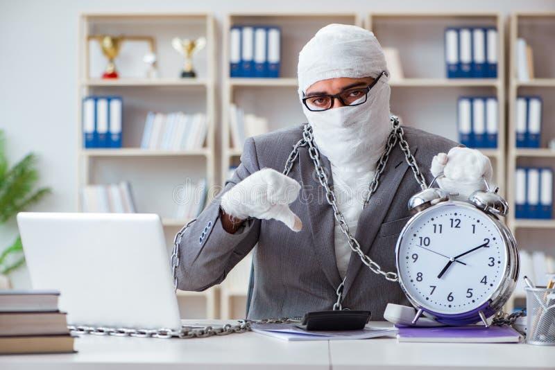 Lavoratore bendato dell'uomo d'affari che lavora nell'ufficio che fa paperwor immagine stock