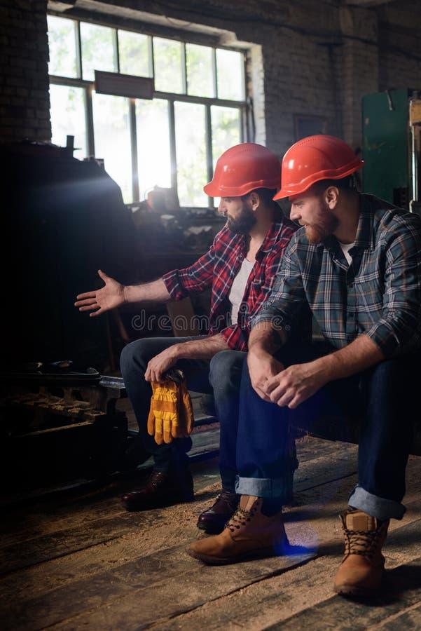 lavoratore in casco protettivo che indica sulla macchina il collega fotografia stock libera da diritti