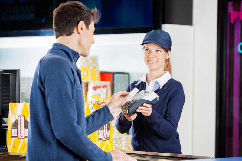 Lavoratore che accetta pagamento dall'uomo con NFC fotografie stock