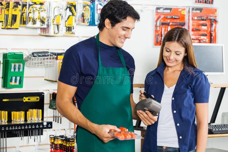Lavoratore che accetta pagamento dalla donna in hardware fotografia stock