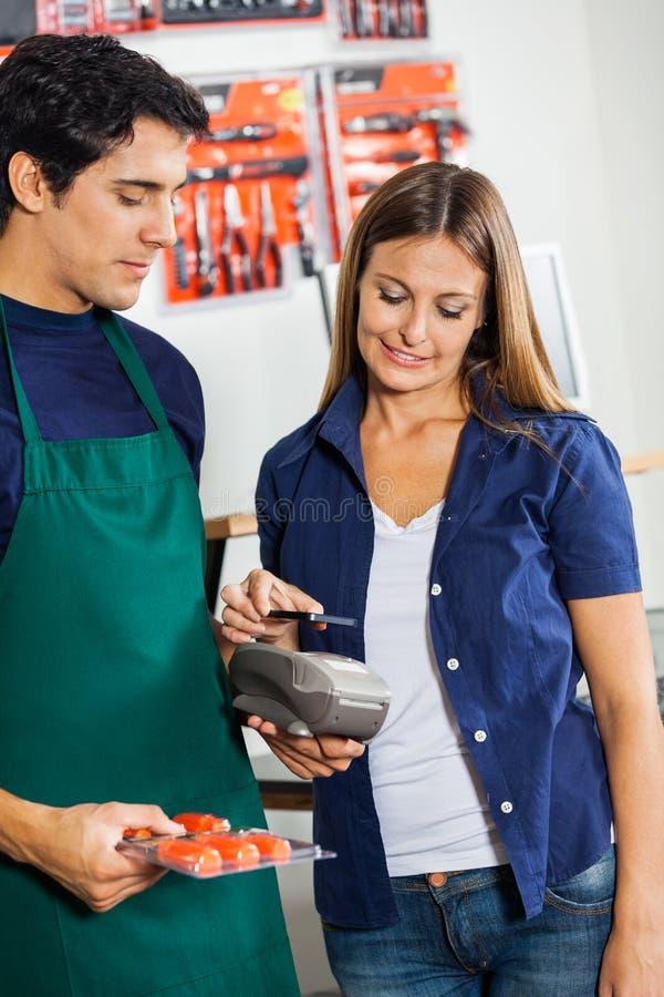 Lavoratore che accetta pagamento dalla donna in hardware fotografie stock libere da diritti
