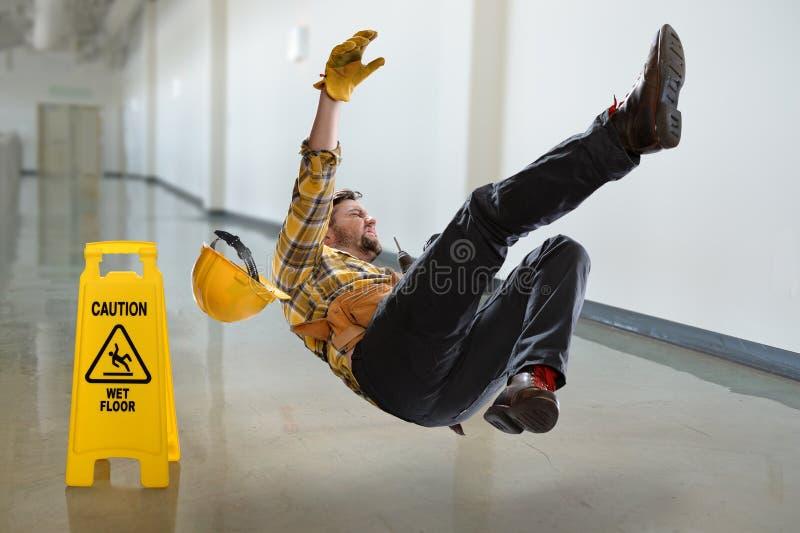 Lavoratore che cade sul pavimento bagnato fotografia stock