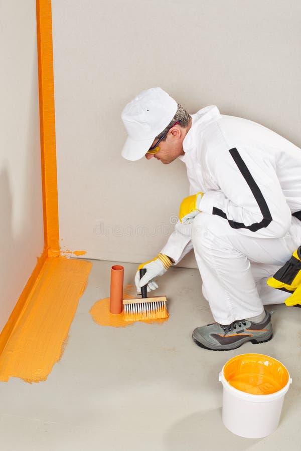 Lavoratore che impermeabilizza intorno alla parete, al pavimento ed al sifone fotografia stock libera da diritti