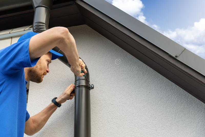 Lavoratore che installa la grondaia del tetto della casa immagine stock libera da diritti