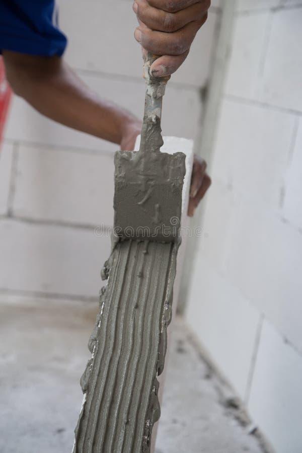 Lavoratore che intonaca il blocco in calcestruzzo leggero della pila, concr spumato immagini stock libere da diritti